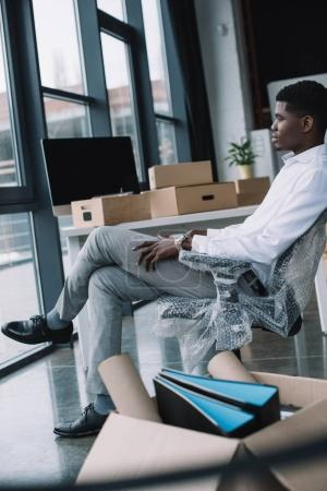 young african american businessman looking at window while sitting in new office during relocation