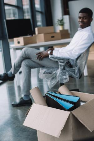 close-up view of cardboard box with office supplies and african american businessman sitting behind in new office