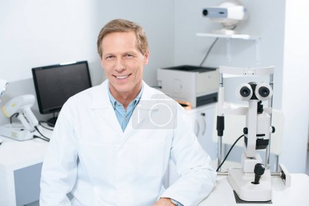 handsome smiling ophthalmologist looking at camera in consulting room