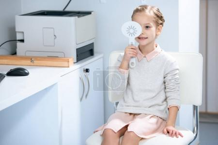 adorable child examining vision and covering one eye at oculist consulting room