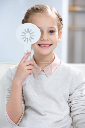 smiling child examining vision and covering one eye at oculist consulting room
