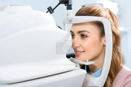 young woman at ophthalmologist consulting room examining vision