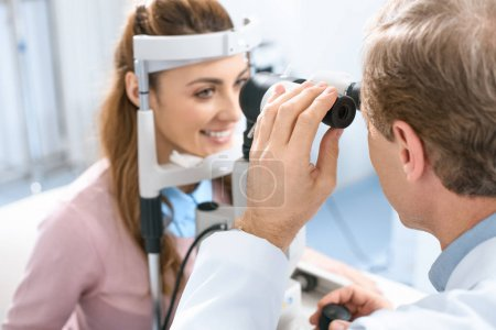oculist examining patient vision with slit lamp in clinic