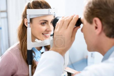 ophthalmologist examining patient vision with slit lamp in clinic