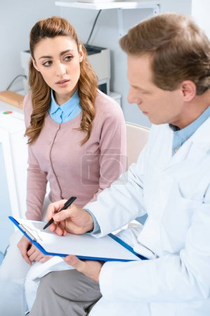 patient looking at ophthalmologist writing something to clipboard in clinic