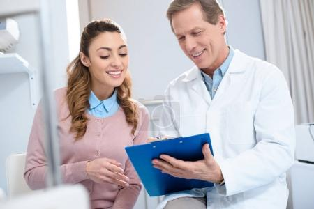 handsome doctor showing something in clipboard to smiling patient in clinic