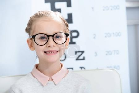 Photo for Adorable child looking at camera in glasses at oculist consulting room - Royalty Free Image