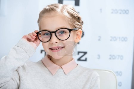 Photo for Adorable smiling child looking at camera in glasses at oculist consulting room - Royalty Free Image