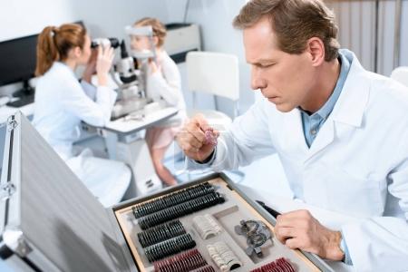 Augenarzt hält Linsen für Versuchsrahmen, während Kollege Kind mit Gesichtsfeldtest untersucht
