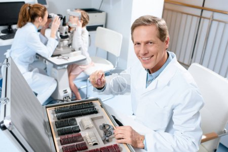 Photo pour Optométriste masculin tenant des lentilles pour cadre d'essai tout en collègue examinant enfant avec test de champ visuel - image libre de droit