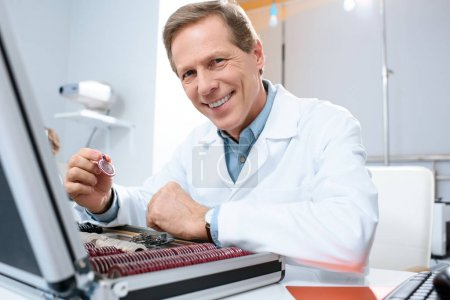 smiling male optician holding lenses for trial frame in clinic