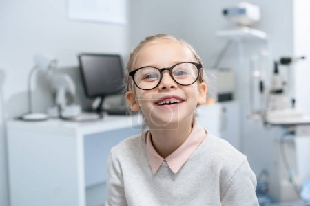 smiling little child in glasses in optical clinic