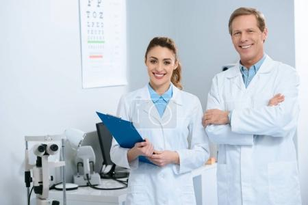 smiling ophthalmologists standing with diagnosis in clinic