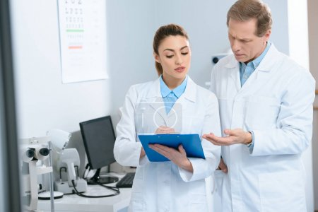 male and female optometrists writing diagnosis in clinic