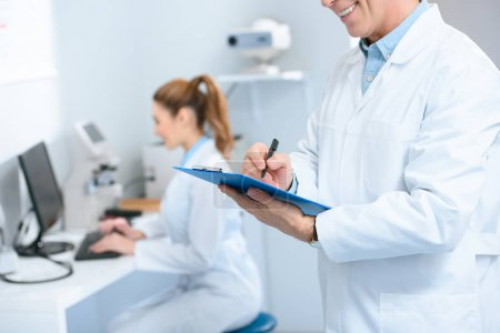 cropped view of male optometrist writing diagnosis while colleague using with computer in clinic