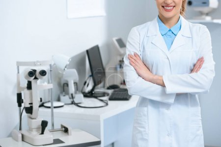 cropped view of female ophthalmologist standing with crossed arms in optical clinic