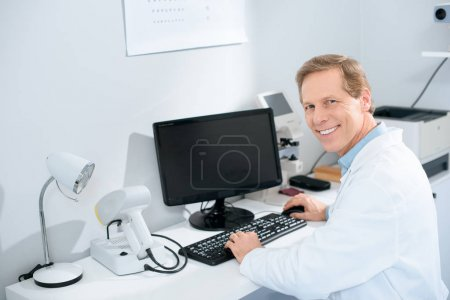 smiling male optician working with computer in clinic
