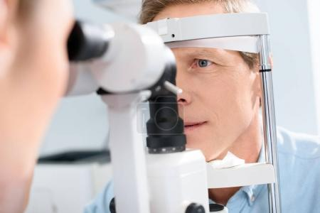 optometrist examining man with modern optical equipment