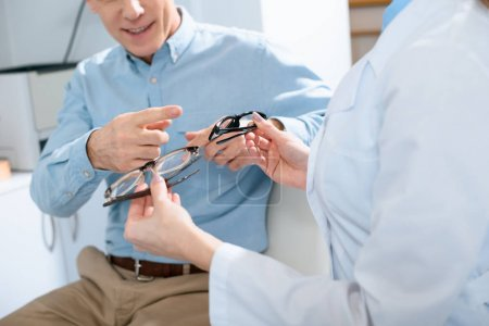 cropped view of man choosing glasses in optical clinic