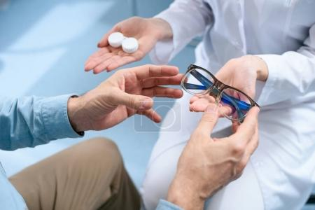 cropped view of man choosing eyeglasses or contact lenses in optical clinic