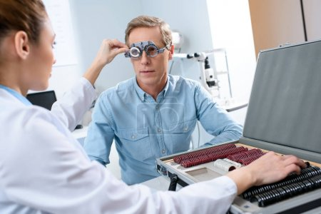 female ophthalmologist examining middle aged man eyes with trial frame