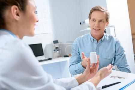 female doctor holding bottle of pills and talking with mature patient in clinic