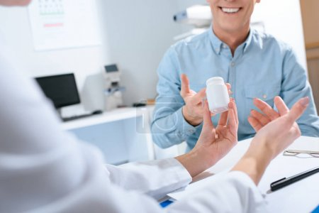 Photo for Cropped view of doctor holding bottle of pills and talking with patient in clinic - Royalty Free Image