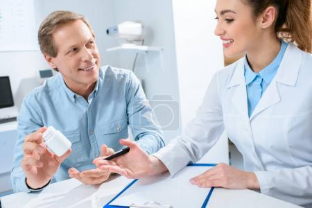 man holding bottle of pills and having consultation with beautiful doctor in clinic