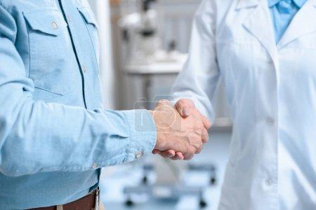 Photo pour Vue partielle de l'homme serrant la main du médecin à la clinique - image libre de droit