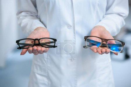 Photo pour Vue recadrée de l'optométriste tenant différentes lunettes dans les mains - image libre de droit