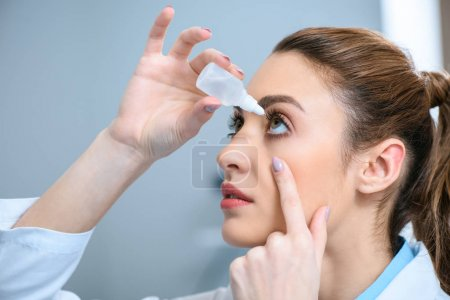 female optometrist dripping eye drops