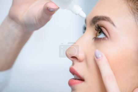 Photo for Profile of beautiful woman dripping eye drops - Royalty Free Image