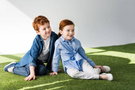 adorable happy redhead kids sitting together on grass and looking away on grey