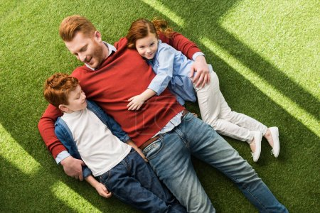 Photo for Top view of happy redhead father with kids lying together on green grass - Royalty Free Image