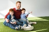 """Постер, картина, фотообои """"Счастливый отец с милые маленькие дети сидели на траве и глядя на серый"""""""