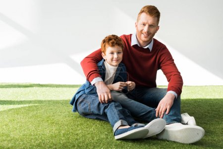 happy father and son sitting on grass and smiling at camera on grey