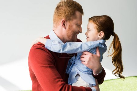 Photo for Happy redhead father and daughter hugging and smiling each other on grey - Royalty Free Image