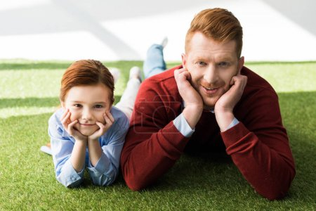 happy redhead father and daughter lying on grass and smiling at camera on grey