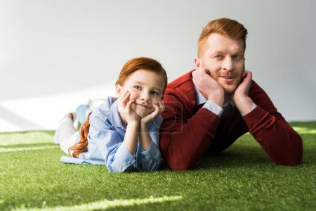 happy redhead father and daughter lying on grass and smiling on grey
