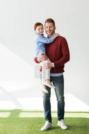 happy father carrying adorable little daughter and smiling at camera on grey