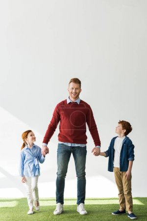 happy father with adorable smiling kids holding hands while standing on grass