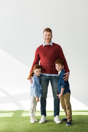 happy father with adorable redhead children standing together on grass and smiling at camera on grey