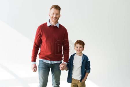 happy redhead father and son holding hands and smiling at camera on grey