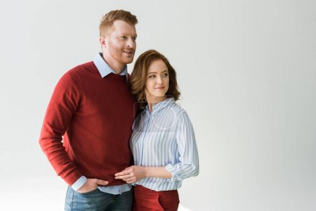 portrait of beautiful redhead couple standing together and looking away isolated on grey