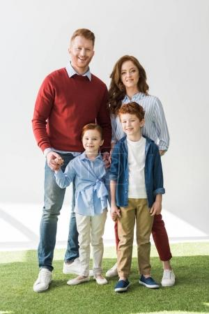 happy redhead family standing together and smiling at camera on grey