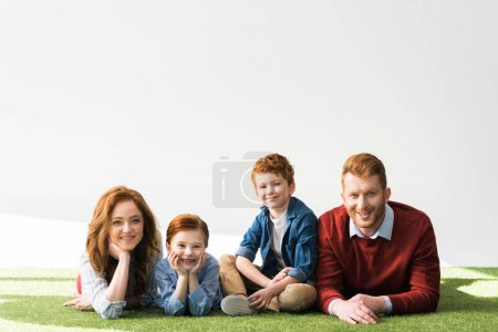 Photo for Beautiful happy redhead family lying on grass and smiling at camera on grey - Royalty Free Image