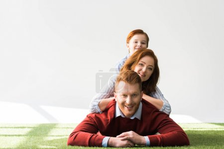 happy red haired family with one kid lying together on grass and smiling at camera on grey