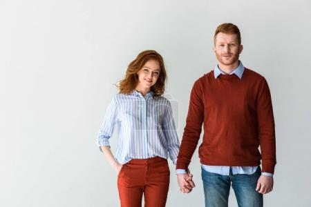 happy redhead couple holding hands and smiling at camera isolated on grey