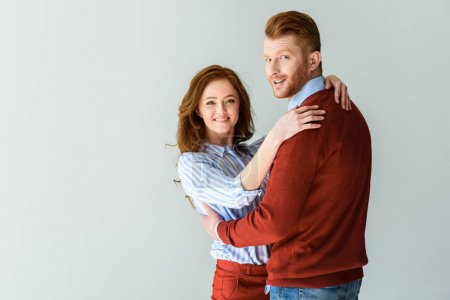 beautiful happy red haired couple hugging and smiling at camera isolated on grey