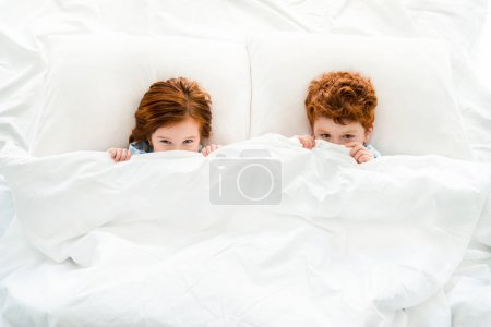 top view of cute little redhead children hiding under blanket in bed